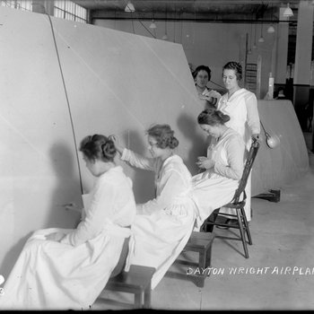 Female employees of the Dayton-Wright Airplane Company attach fabric to the skeleton of an aircraft wing
